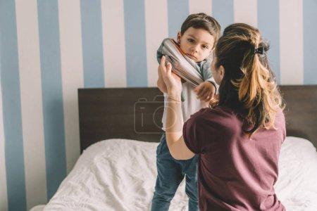 Photo pour Vue arrière d'une mère habillage adorable fils dans la chambre - image libre de droit