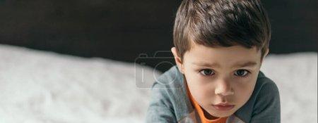 Photo pour Image horizontale d'un garçon réfléchi allongé sur son lit à la maison - image libre de droit