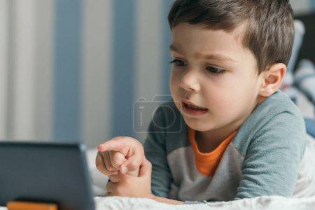 Photo pour Foyer sélectif de petit garçon pointant du doigt le smartphone tout en étant couché dans le lit - image libre de droit