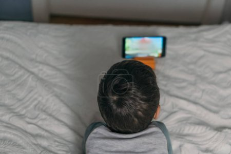 Photo pour Vue aérienne d'un enfant regardant une leçon en ligne alors qu'il était allongé sur son lit - image libre de droit