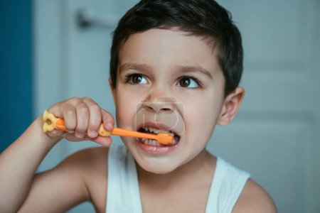 Photo for Cute little boy looking away while brushing teeth in bathroom - Royalty Free Image
