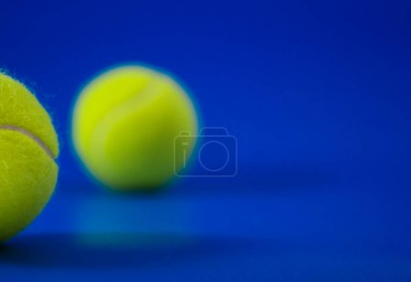two new tennis balls on blue court with light from left, shadow and copy space on right