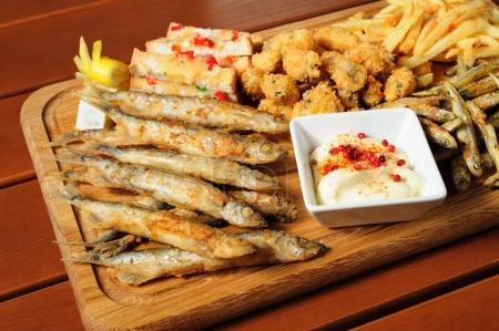 Photo for Big wooden board with fried fush, mussels, french fries served as companion for beer or other alcool drinks - Royalty Free Image