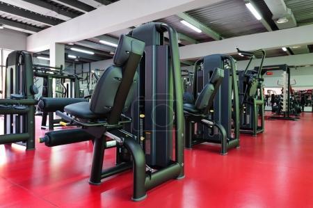 Photo pour Intérieur moderne de salle de gym avec équipement de machine, plancher rouge et réflexes verts de la droite, copyspace - image libre de droit