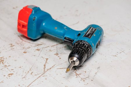 Photo for Old used cordless electric screwdriver at working surface - Royalty Free Image