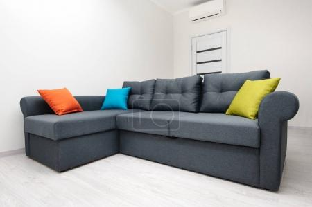Photo for Grey sofa with colored pillows in white room - Royalty Free Image