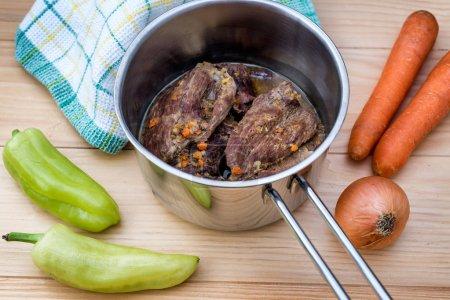 traditionell zubereitete Rindersteaks in Sauce mit Karotten und Zwiebeln, die als Nahaufnahme in einer gusseisernen Saucenpfanne auf einem Holztisch angeboten werden