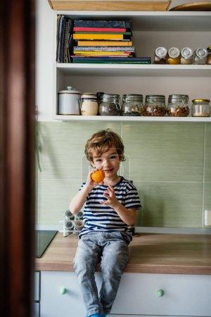 Photo pour Petit garçon dans la cuisine tenant l'orange - image libre de droit