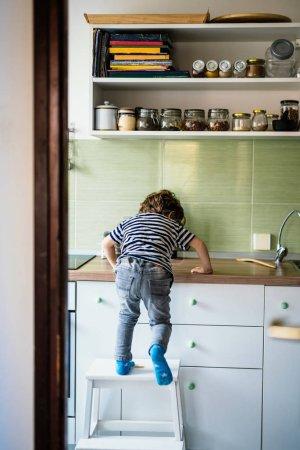 Photo pour Petit garçon grimpant sur un comptoir dans sa cuisine - image libre de droit