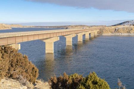 Lac bleu avec pont reliant de vastes terrains recouverts de neige en hiver