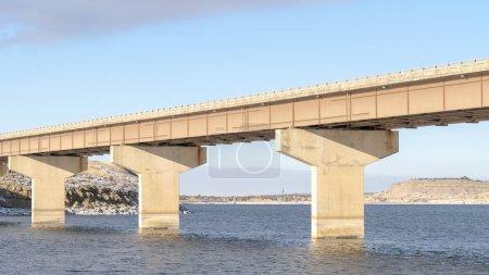 Panorama Pont Stringer traversant un lac bleu et reliant des terrains rocheux enneigés