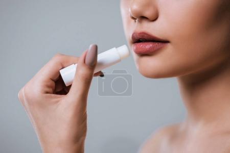 Photo pour Image recadrée d'une jeune femme séduisante utilisant du baume à lèvres sur fond gris. Soins aux femmes - image libre de droit