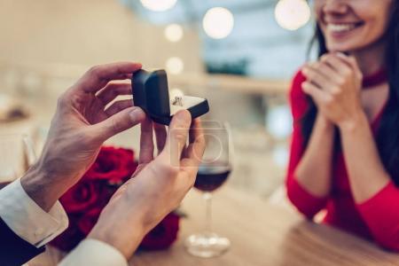 Photo pour Image recadrée de couple amoureux passe du temps ensemble dans un restaurant moderne. Attrayant jeune femme en robe et bel homme en costume ont dîner romantique. Célébration de la Saint Valentin . - image libre de droit