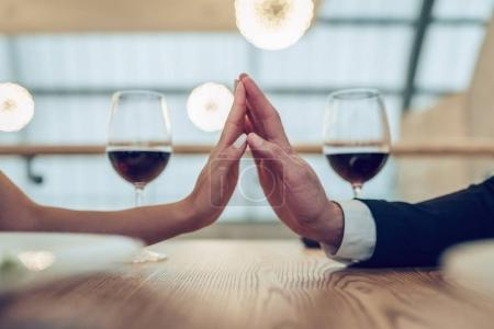 Photo for Cropped image of loving couple is spending time together in modern restaurant. Attractive young woman in dress and handsome man in suit are having romantic dinner. Celebrating Saint Valentine's Day. - Royalty Free Image