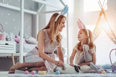 Photo pour Attrayant jeune femme avec petite fille mignonne se préparent pour la célébration de Pâques. Maman et fille portant des oreilles de lapin s'amusent avec lapin de Pâques tout en étant assis sur le sol à la maison . - image libre de droit