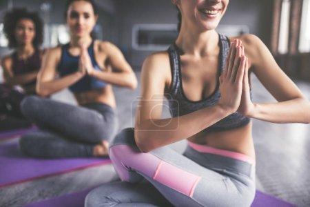 Photo pour Les filles séduisantes jeunes sport font yoga ensemble. Formation de groupe. Concept de mode de vie sain. - image libre de droit