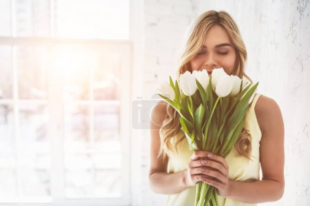 Photo for Portrait of attractive young woman with tulips is standing in light room and smiling. Happy international women's day! Celebrating 8th of March. - Royalty Free Image