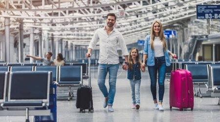 Photo pour Famille à l'aéroport. Attrayant jeune femme, bel homme et leur jolie petite fille sont prêts pour voyager ! Concept de famille heureuse . - image libre de droit