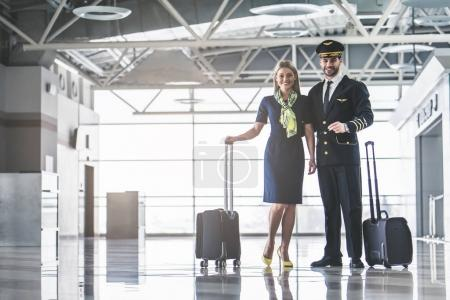 Handsome male pilot and attractive female flight a...