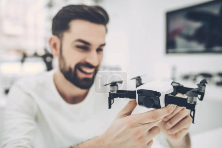 Photo for Handsome young man in modern light quadcopter store. Choosing the appropriate drone - Royalty Free Image
