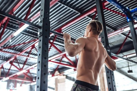 Photo for Strong muscular man is working out in gym. Cross fit training. Shirtless man doing pull ups. - Royalty Free Image