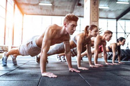 Photo pour Groupe de personnes musclées sportives travaillent dans la salle de gym. Entraînement cross fit. Faire un exercice de planche ensemble . - image libre de droit