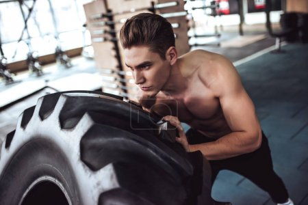 Photo for Strong muscular man is working out in gym. Cross fit training. Pushing tire. - Royalty Free Image