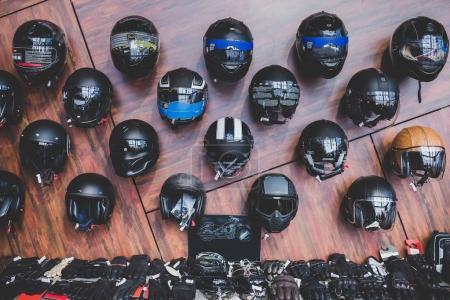 Foto de Motocicletas y accesorios en la tienda de motos modernas. Cosas de moteros. Cascos sobre fondo de madera - Imagen libre de derechos