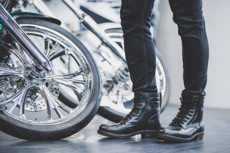 Photo pour Bel homme barbu dans le magasin de motos. Motard est de choisir nouveau véhicule et moto accessoires. Image recadrée de l'homme debout près de vélo. - image libre de droit