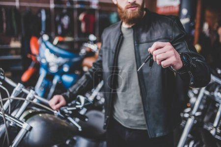 Photo for Cropped image of handsome bearded man in motorcycle shop. Biker is choosing new vehicle and motorcycle accessories. Holding keys. - Royalty Free Image