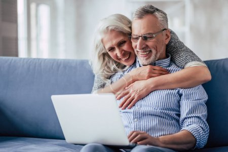 Photo for Love lives forever! Senior couple at home. Handsome old man and attractive old woman are hugging and enjoying spending time together while sitting on sofa with laptop. - Royalty Free Image