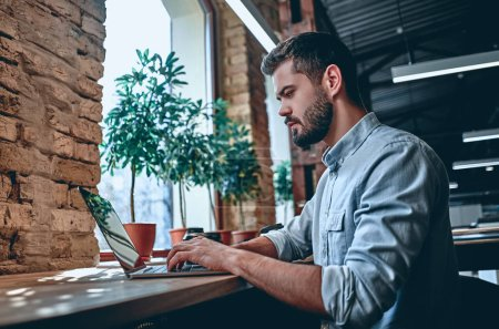 Photo for Young business man is working in modern office with laptop. Freelancers in coworking place. Creative and stylish youth. - Royalty Free Image
