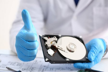 Male repairman wearing blue gloves is holding hard drive
