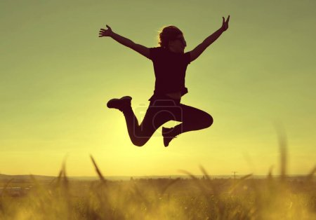 Photo for Young happiness woman jumping high at sunset. - Royalty Free Image