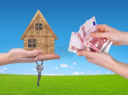 Wooden house with key and Euro money in hands