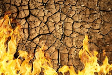 Cracked dry soil of earth texture with fire flames.