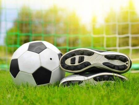 Soccer ball and shoes in grass.