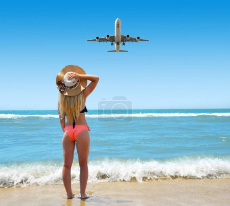 Photo for Caucasian girl with hat on the beach. Woman is looking at landing a passenger airplane. Summer vacation by the sea. - Royalty Free Image