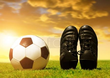 Soccer ball and shoes on football playground.