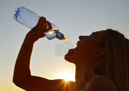 Silhouette of a woman drinking water from bottle.