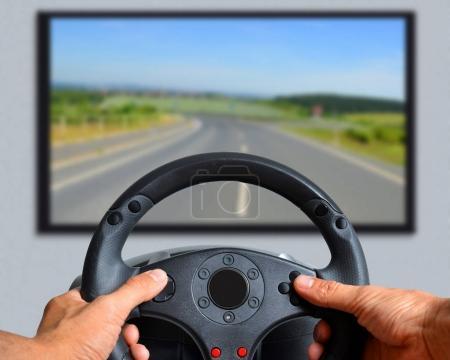 Hands holding gaming steering wheel.