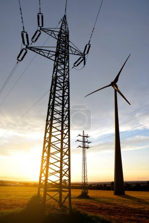 Electricity transmission pylon and wind turbine at sunset.