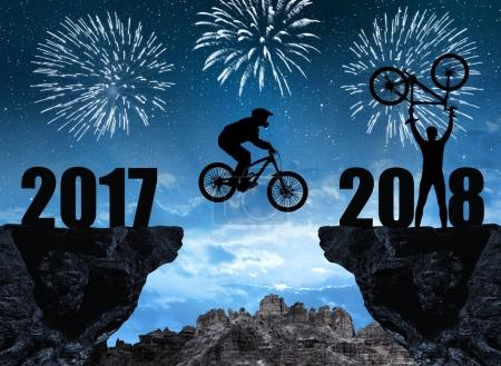 Silhouette cyclist jumping into the New Year 2018.