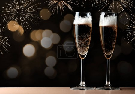 Two glasses with champagne on a table.