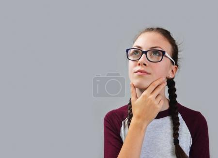 Young thoughtful girl with glasses dreaming.