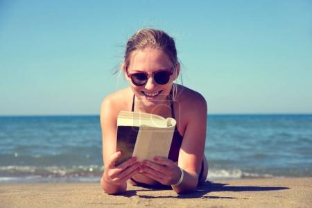 Caucasian girl lying on beach and reading a book.