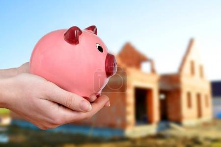 Hands holding pink piggy bank at the background house construction.