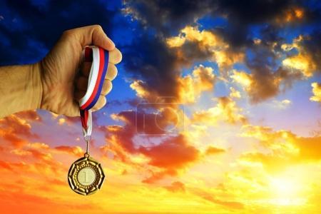 Photo pour Main tenant une médaille d'or contre le ciel couchant . - image libre de droit