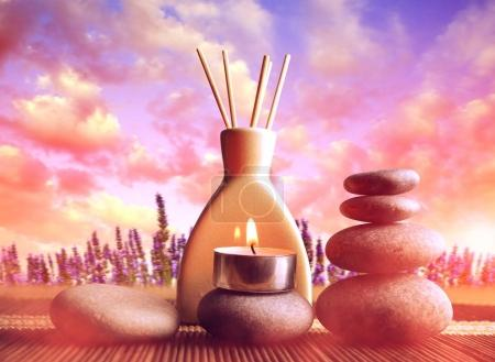 Air freshener with candle and zen pebbles at sunset.