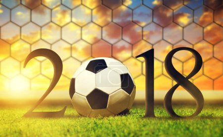 New Year 2018 concept. Soccer ball in grass at sunset.